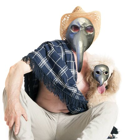 A sick elderly man in a plague mask and sombrero is sitting on the floor, hugging a poodle.
