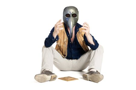 Sick elderly man in antiplague mask and sombrero sitting on the floor