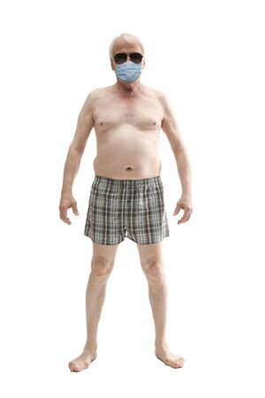 A man in shorts and an antiviral mask rests on the beach 写真素材