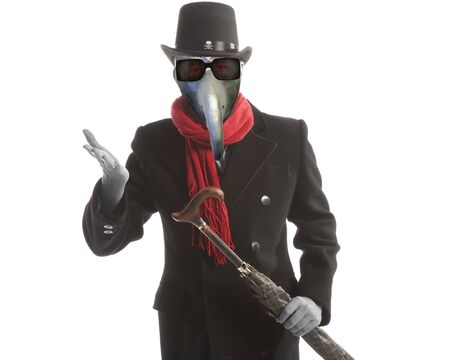 A man in an elegant coat, a plague mask with a cane and  in a hat in the image of a devil posing on a white background