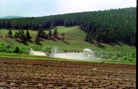 Artificial irrigation of future crop seedlings in a field among the mountains