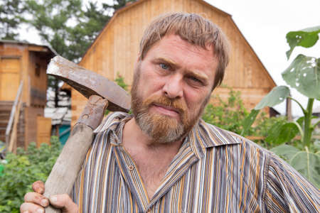 Russian man with a blunt ax for splitting large chocks
