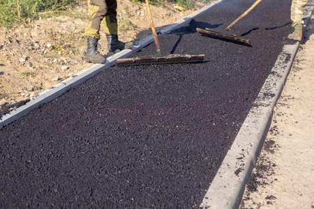 On the sidewalk, road workers leveling freshly laid hot asphalt