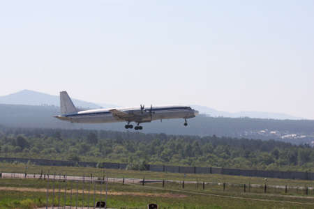 Passenger retro turboprop four-engine aircraft takes off and gains altitude