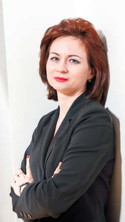 Photoshoot of an intellectual business woman in a black business suit on a white background