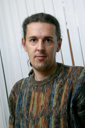 Stylish young man in sweater is photographed while talking