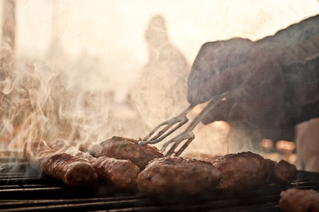 hand with a fork touches meat on barbecue