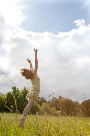 Geringer Kontrast Bild einer glücklichen Frau auf Feld springt zum Himmel