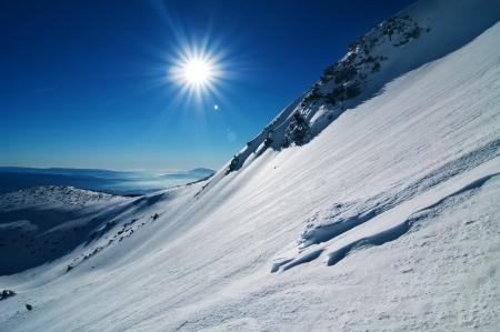 Blue sky, snow capped hills photo