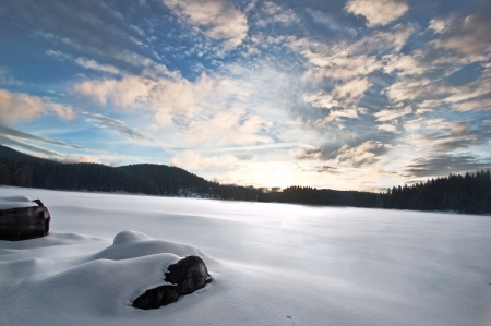 Frozen lake, moody sky at sunset