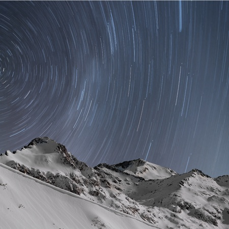 Winter landscape  Star trails, snow capped mountains, long exposure photo