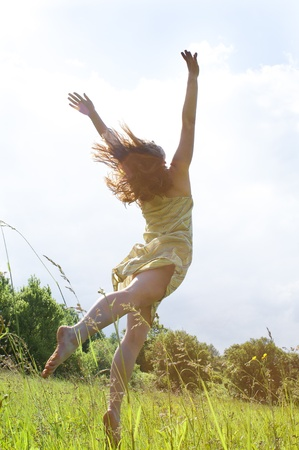 outstretched arms: Happy woman in dress Jumping to the sky, shootet from her back, low contrast