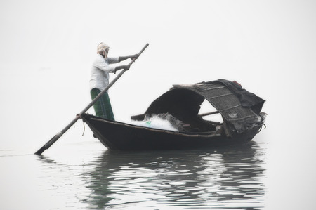 Fisherman rowing on a boat photo
