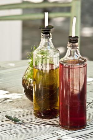 vinegar bottle: Bottles of olive oil and vinegard at table