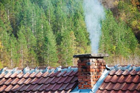 Rauchender Kamin am Wald Hintergrund Standard-Bild