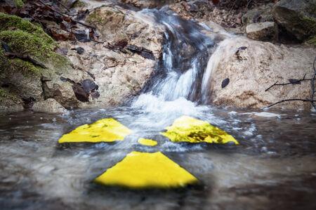 pollutants: Radioactive symbol in river flow.