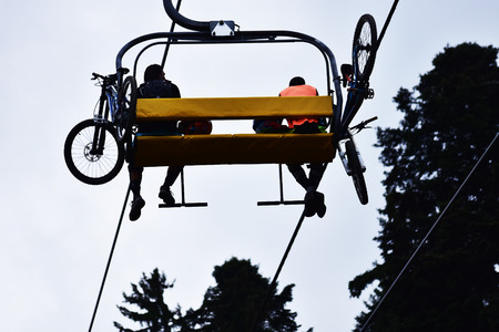 chair on the lift: Mountain bikers on a chair lift in the mountain. Stock Photo