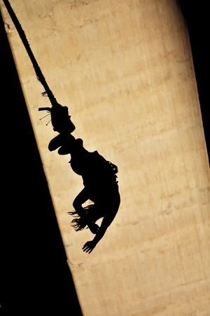 Bungee jumps, extreme and fun sport. Silhouette at bridge column.