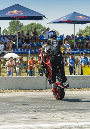 entertain: Vinnytsia,Ukraine-July 25, 2015: Unknown stunt biker entertain the audience before the start of the championship of drifting   on July 25,2015 in Vinnytsia, Ukraine.