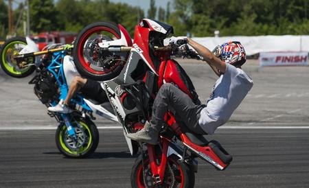 lLviv, Ukraine - June 7, 2015: Unknown stunt bikers  entertain the audience before the start of the championship of drifting near Arena - Lviv stadium in Lviv, Ukraine.