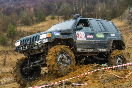 Lviv, Ukraine - February 21, 2016: Off-road vehicle brand Jeep Cherokee overcomes the track on a amateur competitions Trial near the city Lviv, Ukraine.