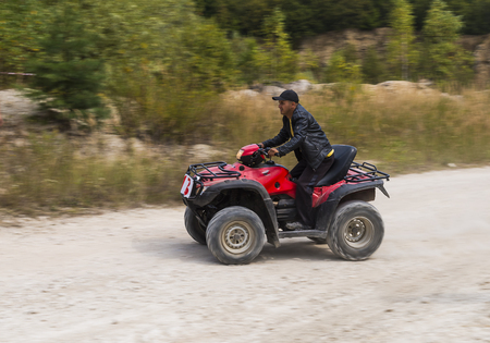 Lviv, Ukraine - August 23, 2015: ATV overcomes the track on of sandy career near the city Lviv, Ukraine.