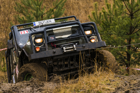 Lviv, Ukraine - February 21, 2016: Off-road vehicle UAZ (No. 221) overcomes the track using winch on of landfill near the city Lviv. Editorial