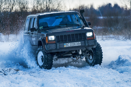 Lviv, Ukraine - December 04, 2016: Unknown racers  on off-road vehicle Jeep Cherokee overcomes the track at amateur competitions among off-road vehicles near ringroad of  the city Lviv, Ukraine