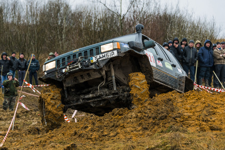 Lviv, Ukraine - February 21, 2016: Off-road vehicle brand Jeep Cherokee overcomes the track on a amateur competitions Trial near the city Lviv, Ukraine. Audience watching the competitions.