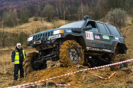 Lviv, Ukraine - February 21, 2016: Off-road vehicle brand Jeep Cherokee overcomes the track on a amateur competitions Trial near the city Lviv, Ukraine. Referee watching the competitions.