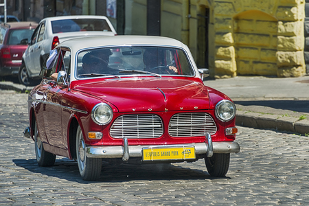 reenactment: Lviv, Ukraine - June 4, 2017: Old retro car VOLVO AMAZON 121 with its owner and au unknown passengers taking participation in race Leopolis grand prix 2017, Ukraine.