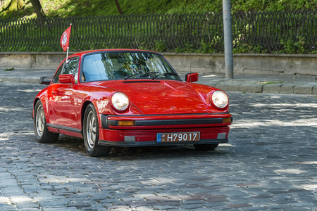 Lviv, Ukraine - June 4, 2017:Old retro car Porsche 911 with its owner and an unknown passenger taking participation in race Leopolis grand prix 2017, Ukraine.