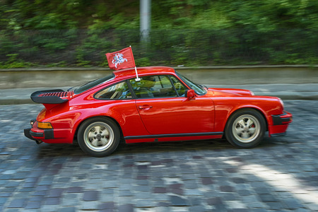 Lviv, Ukraine - June 4, 2017:Old retro car Porsche 911 with its owner and an unknown passenger taking participation in race Leopolis grand prix 2017, Ukraine.