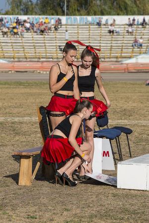Rivne, Ukraine - 29 August 2015: Pit lane girls getting ready for a competition on the Open Cup Speedway to the day of the city Rivne