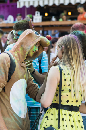 Lviv, Ukraine - August 30, 2015: Guy in a suit deer entertains Woman during the festival of color in a city park in Lviv.