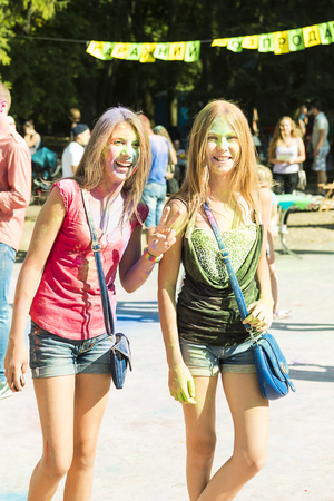 Lviv, Ukraine - August 30, 2015: Girls twins have fun during the festival of color in a city park in Lviv. Editorial
