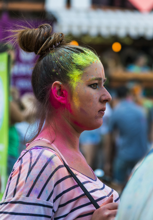 Lviv, Ukraine - August 30, 2015: Girl  watching festival of colors in a city park in Lviv.