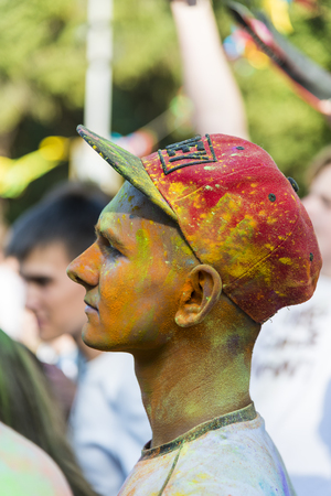 Lviv, Ukraine - August 30, 2015: Man with baseball cap on the head  watches festival of colors in a city park in Lviv.