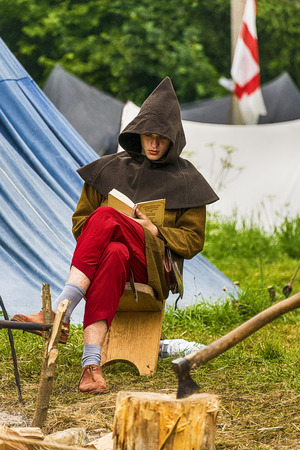 executor: Urych, Ukraine - August 6,2016: Tustan Medieval Culture Festival in Urych, Western Ukraine, on August 6, 2016.Executioner reading a book before execution. Editorial