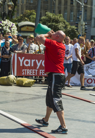 Lviv, Ukraine - July 05, 2015: Strongman inflates a rubber hot water bottle in Yarych street Fest 2015  near centrum  of  Lviv city. Editorial