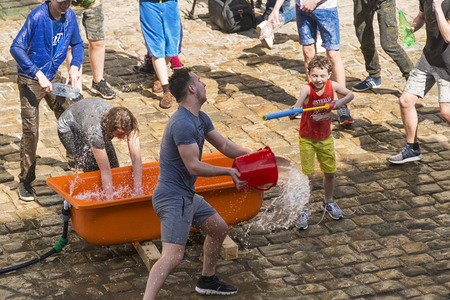 Lviv , Ukraine - April 09 2018: Ð¡elebrations Clean Monday (or Wet Monday), a Ukrainian Christian tradition celebrated on the first day after Orthodox Easter. Young people spray water on one another and   funy  near the town hall  ,  Lviv, Ukraine.