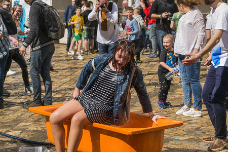 Lviv , Ukraine - April 09 2018:  Сelebrations  Wet Monday, a Ukrainian Christian tradition celebrated on the first day after Orthodox Easter.  Wet girl gets up from the bath near the town hall. Lviv, Ukraine.
