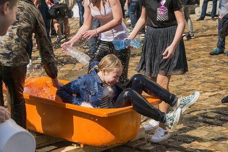 Lviv, Ucraina - 9 aprile 2018: Ð¡elebrations Wet Monday, una tradizione cristiana ucraina celebrata il primo giorno dopo la Pasqua ortodossa. La ragazza bagnata si alza dal bagno vicino al municipio. Lviv, Ucraina.