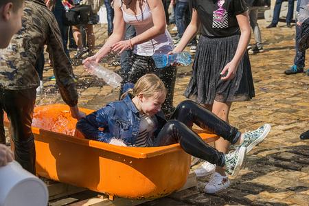 Lviv, Ucrania - 09 de abril de 2018: Ð¡elebrations Wet Monday, una tradición cristiana ucraniana celebrada el primer día después de la Pascua ortodoxa. Chica mojada se levanta del baño cerca del ayuntamiento. Lviv, Ucrania.