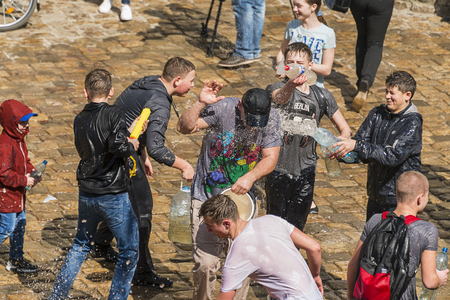 Lviv , Ukraine - April 09 2018:  Ð¡elebrations  Wet Monday, a Ukrainian Christian tradition celebrated on the first day after Orthodox Easter. Young people spray water on one another and   funy  near  the town hall  ,  Lviv, Ukraine.