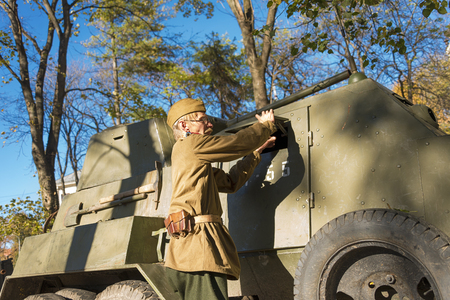Lviv, Ukraine – Oktober,14, 2018: Military historical reconstruction is dedicated to The anniversary of the creation of the Ukrainian Insurgent Army. Soldier prepares armored car for battle. Editorial