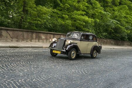Lviv, Ukraine - June 2, 2019: Old retro car  Opel 1.3 mobel 1397 (1934) with its owner and  unknown passenger taking participation in race Leopolis grand prix 2019, Ukraine.