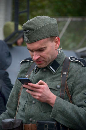 Lviv, Ukraine - October, 14, 2020: Military historical reconstruction is dedicated to the anniversary of the creation of the armed forces. The participant of the reconstruction uses cellular communication.