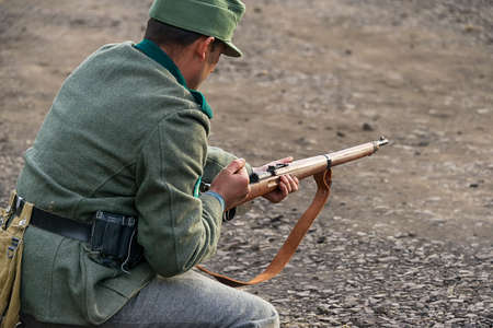 Lviv, Ukraine October, 14 - 2020: Military historical reconstruction is dedicated to the anniversary of the creation of the armed forces. Soldier reloading weapon in the vicinity of Lviv.