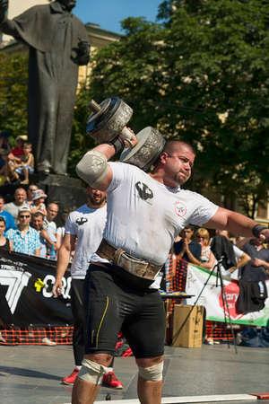 Lviv, Ukraine - July 05, 2015: Strongman competitions raises dumbbell hand in Yarych street Fest 2015 near centrum of Lviv city.